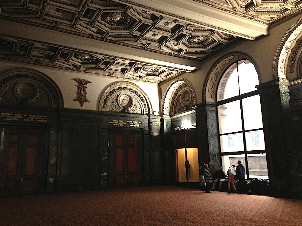 An a cappella group sings in a grand room at the Chicago Cultural Center. Courtesy of Ally Marotti.