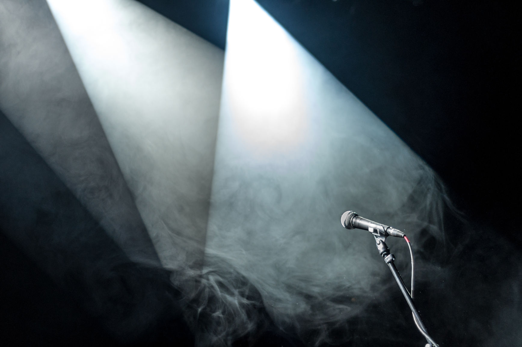 A Microphone In A Spotlight On A Stage