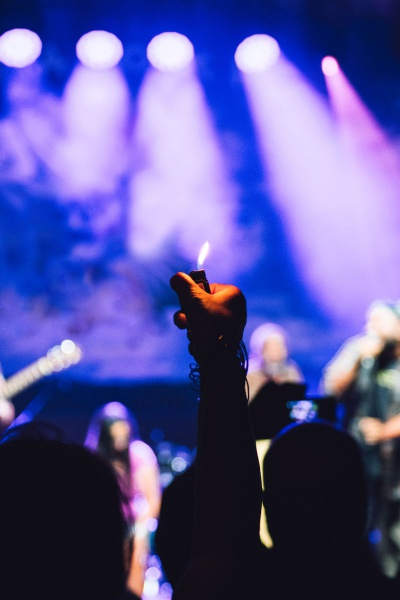 Hand Holding Lit Lighter At Music Concert