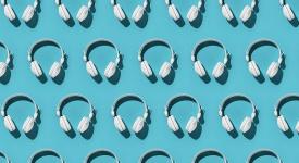dozens of white headphones against an aqua background