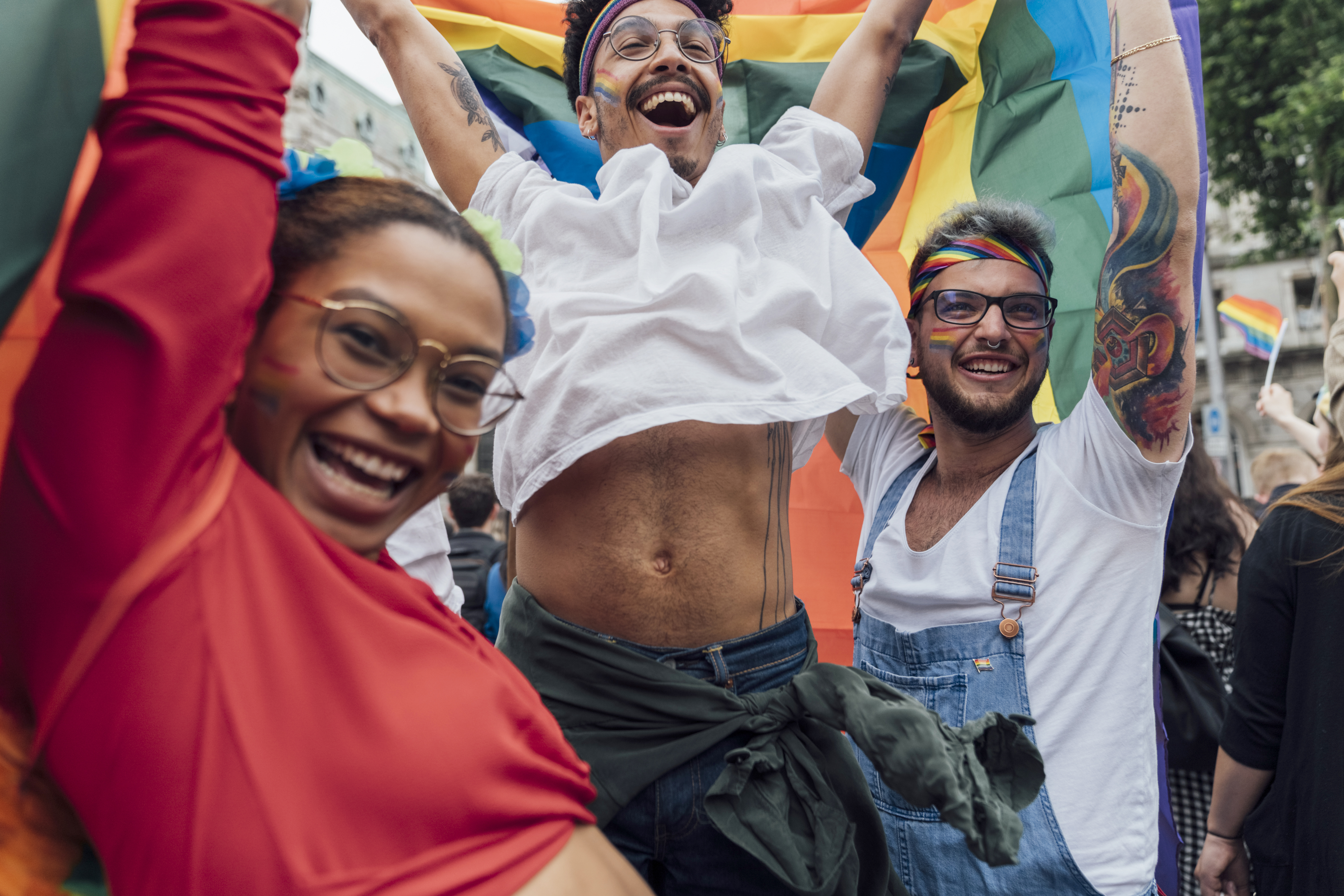 Group of Friends Jumping, Laughing and showing Positive Vibes at the Gay Pride Waving Colourful Rainbow Flags in the Middle of the Busy Street