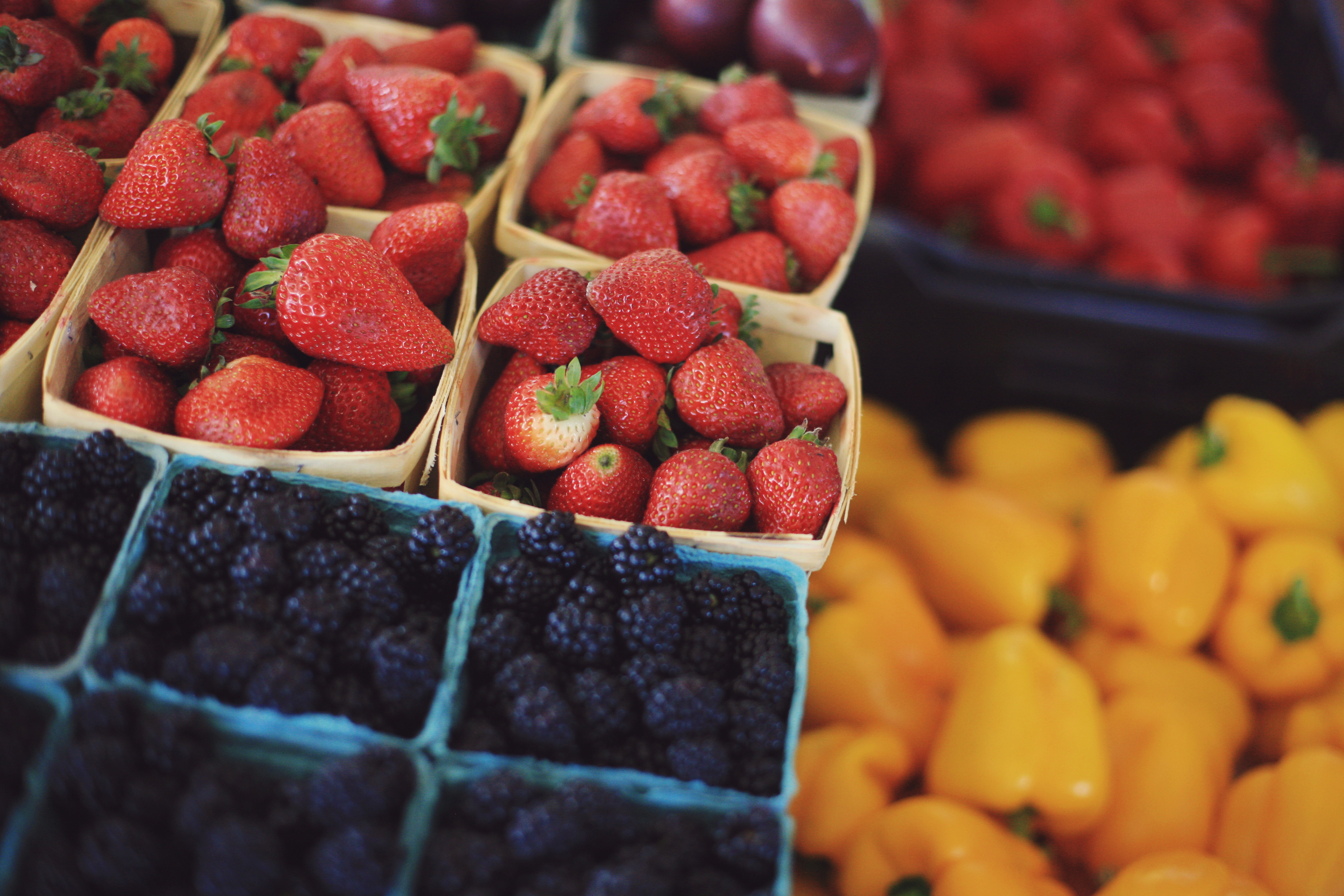 A table of fresh picked berries and peppers at a local mid-west farmer's market.
