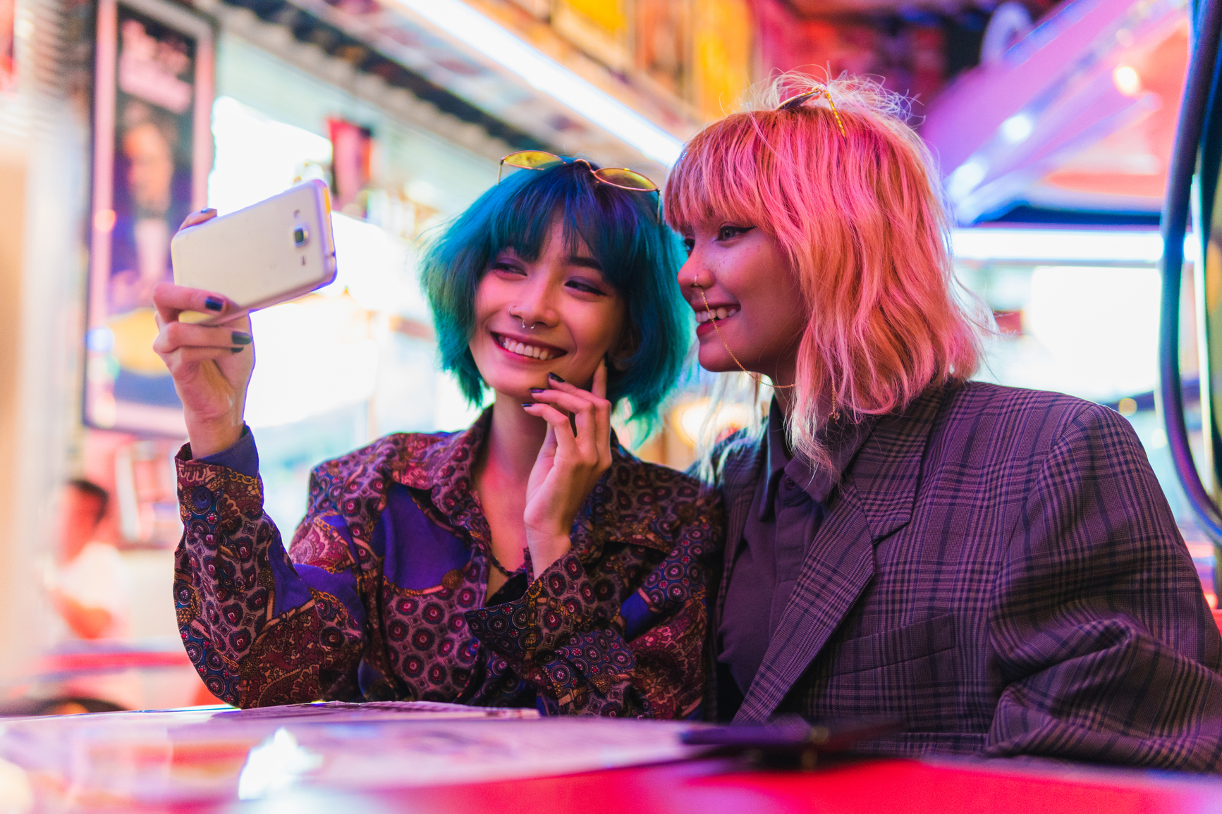 Stock photo of two asian alternative girls with pink and green hair, sitting in a diner inside taking a selfie smiling.