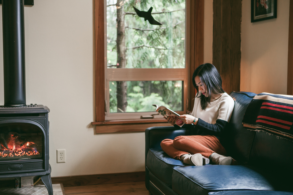 Vietnamese woman in her late 20's reading a magazine on her blue leather couch in a cabin with a fire