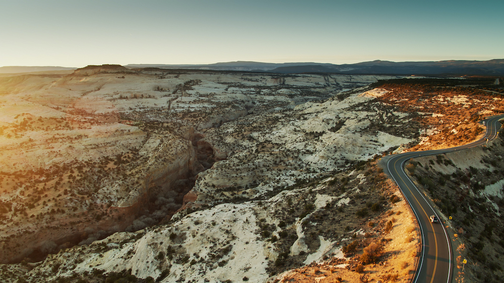 Aerial shot of a car with a roof box on a road on a ridge above Calf Creek in Grand Staircase-Escalante National Monument, Utah at sunrise.