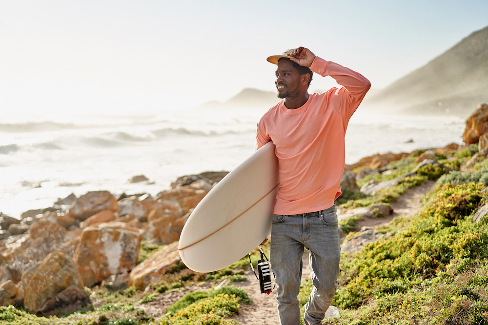 A young Black surfer walks along a scenic rocky coastline looking for surf. He is carrying his surfboard on his way to go surfing