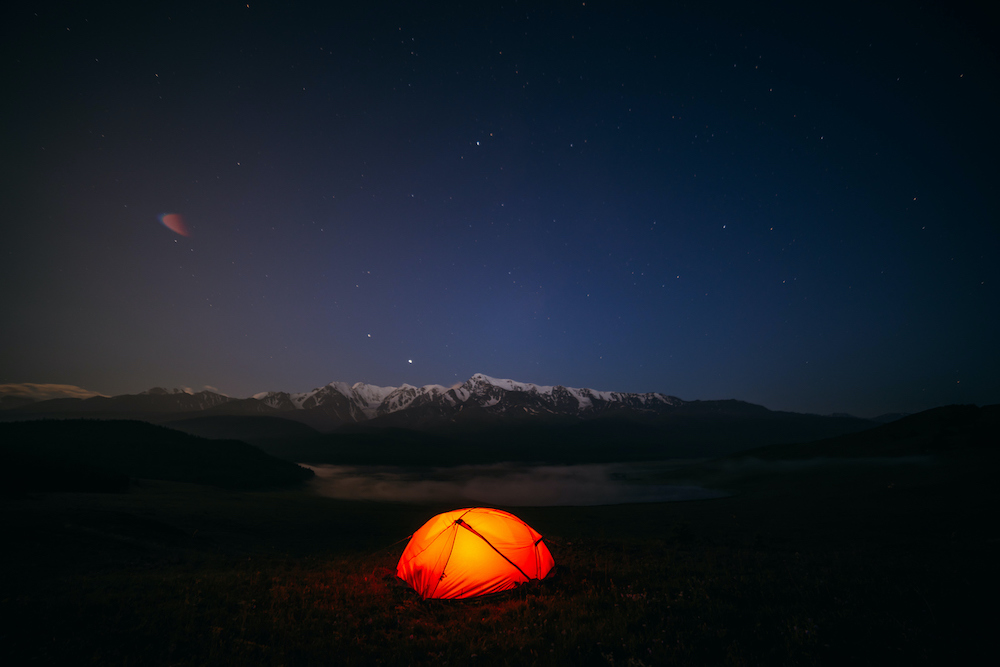 Atmospheric mountain landscape with vivid orange tent on hill under night starry sky. Tent glow by orange light with view of snowy mountains in starry night. Overnight in nature in great mountains. (Atmospheric mountain landscape with vivid orange ten