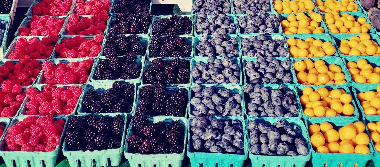 strawberries, blackberries, blueberries on retail display in farmer's market in california