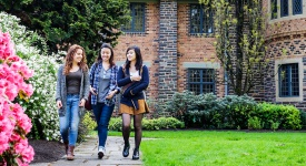 3 female young adults walking on a college campus