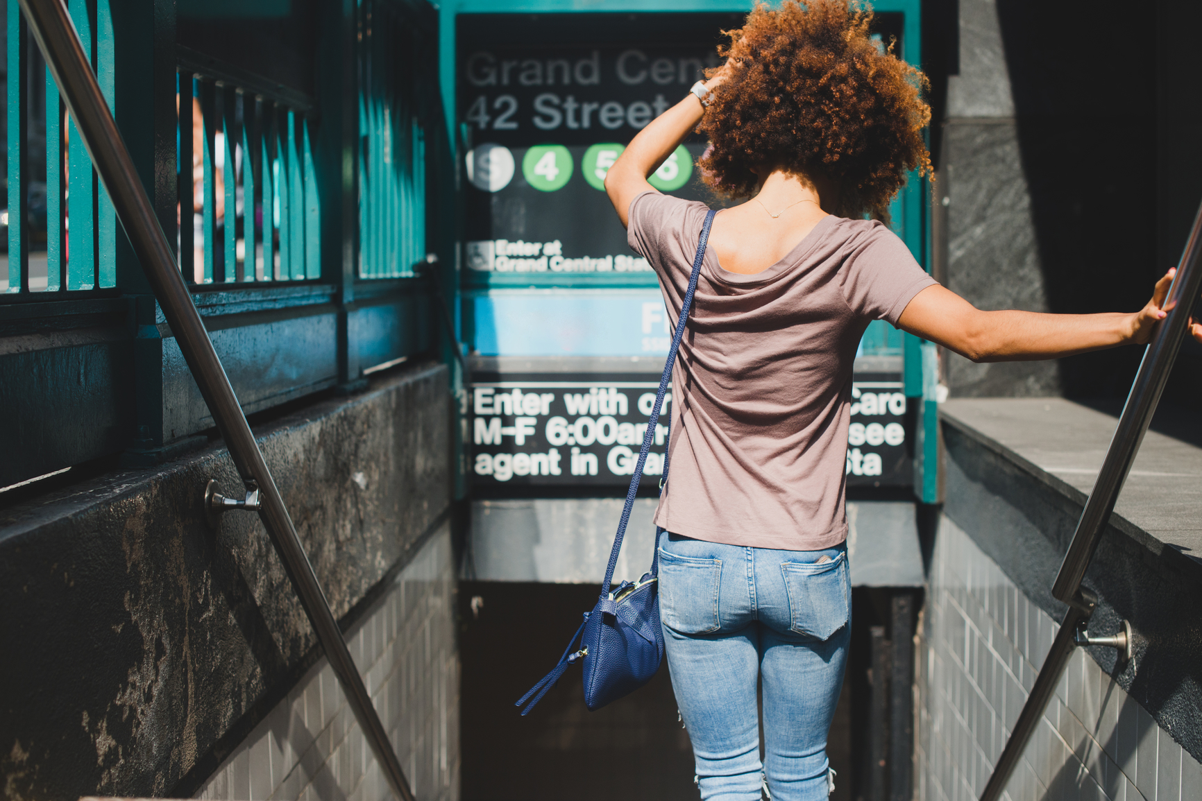 Young woman going down steps to subway entrance in the city